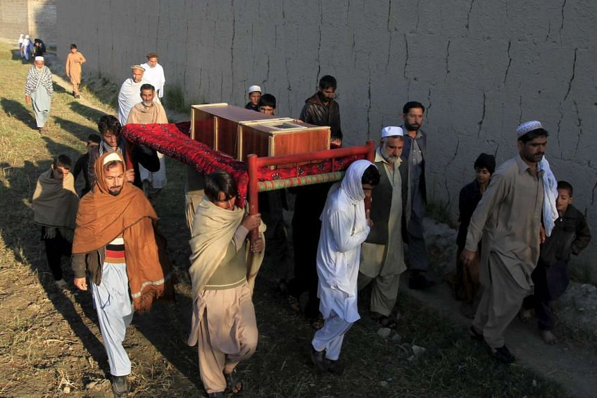 Afghan men carry a coffin of an earthquake victim for burial in Behsud district of Nangarhar province, Afghanistan on Tuesday.