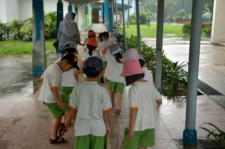 Preschoolers from My First Skool walking under the shelter as their teacher leads the way back to their centre.