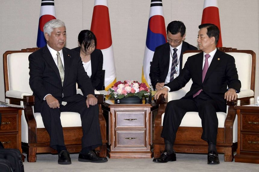 South Korean Defense Minister Han Min-Koo (right) talks with Japanese Defence Minister Gen Nakatani (left) during their meeting at the Defense Ministry in Seoul, South Korea, on Oct 20, 2015.