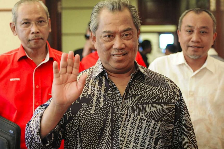 Former Malaysian deputy prime minister Muhyiddin Yassin (centre) waving as he arrives for a United Malays National Organisation supreme council meeting in Kuala Lumpur on Sept 9, 2015.