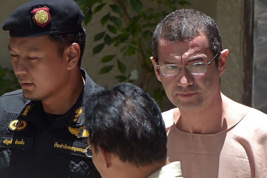 Former PetroSaudi exec Xavier Andre Justo (right), is escorted by Thai officials as he leaves a courthouse in Bangkok on Aug 17, 2015.