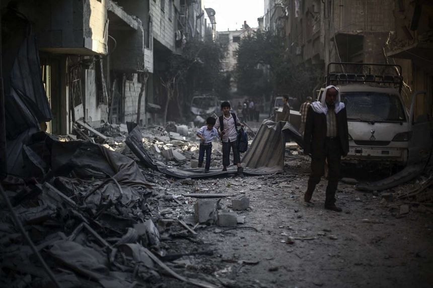 Syrian boys walk amid the rubble of buildings destroyed following an airstrike reportedly conducted by forces loyal to the Syrian Government, in Douma, on the outskirts of Damascus, Syria, on Oct 21, 2015.