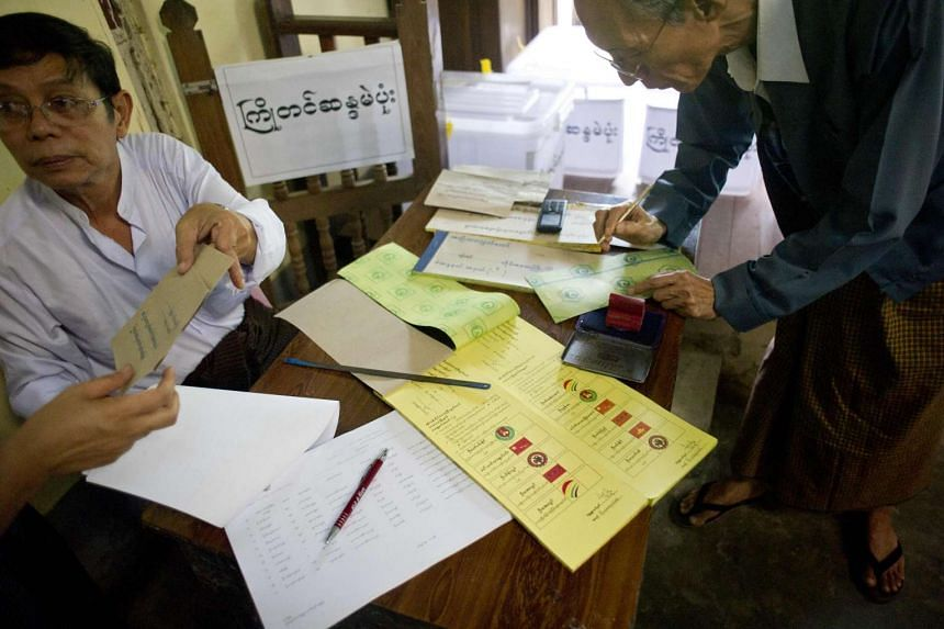 Member of staff at a polling station check ID cards as they prepare for advance voting at a ward administration office on the outskirts of Yangon on Oct 29, 2015.
