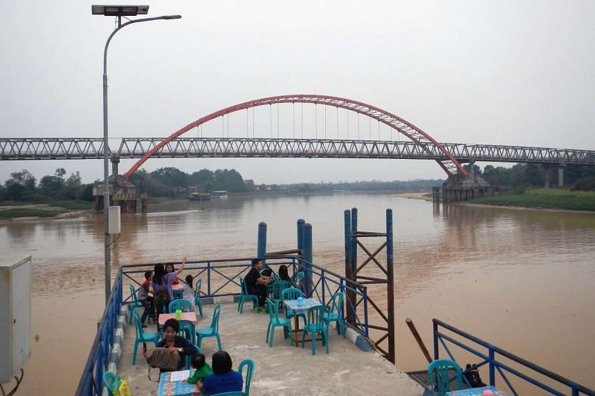 People enjoying the clearer skies while eating dinner at a restaurant near Kahayan river in Palangkaraya, in Central Kalimantan, on Oct 29, 2015.