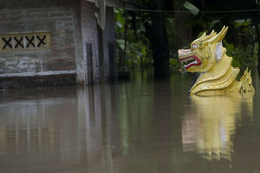 A traditional Myanmar lion statue sinks in floodwaters in Kyouk Ye village near Hinthada town in Myanmar's Irrawaddy region on Aug 6, 2015. Myanmar's president called for the evacuation of low-lying areas as the Irrawaddy river threatened to breach