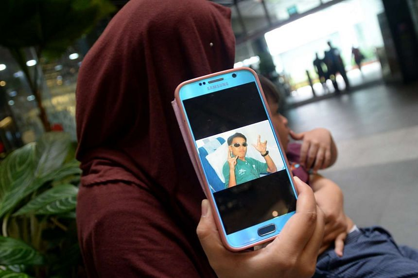 Nurul Asyikin Norman, the widow of the late Mohd Rizalludin Hassan, showing his photograph on her mobile phone.