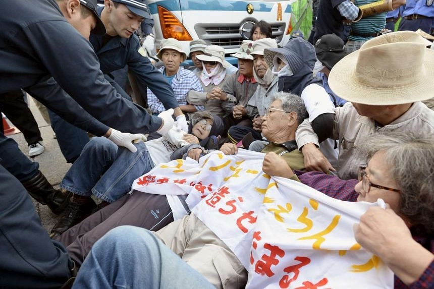 Protesters lying on the ground as they try to block work on a contentious U.S. air base in front of the gate of the U.S. Marine Corps Camp Schwab in Nago on the southern Japanese island of Okinawa, in this photo taken by Kyodo on Oct 29, 2015. Elderl