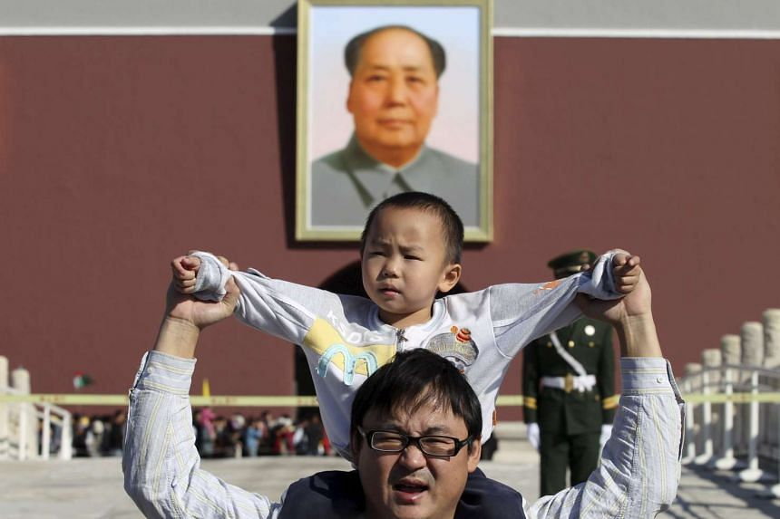 A boy sits on his father's shoulders as they pose for a photograph in front of the giant portrait of late Chinese chairman Mao Zedong on the Tiananmen Gate, in Beijing, China, on Oct 2, 2011. China will ease family planning restrictions to allow all