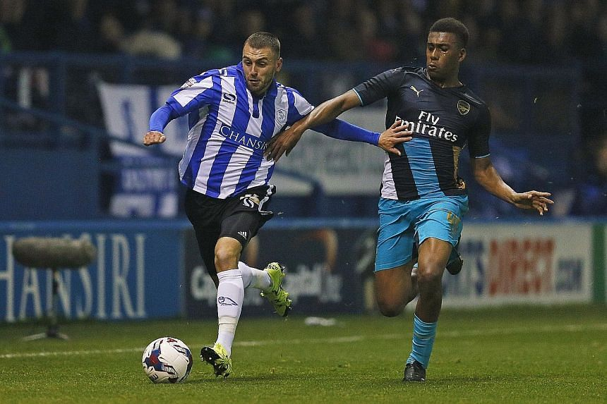 """Sheffield Wednesday's Jack Hunt (left) trying to shrug off Arsenal's Alex Iwobi at Hillsborough on Tuesday. """"It was a bad night at the office,"""" said Arsene Wenger of the 0-3 League Cup loss."""
