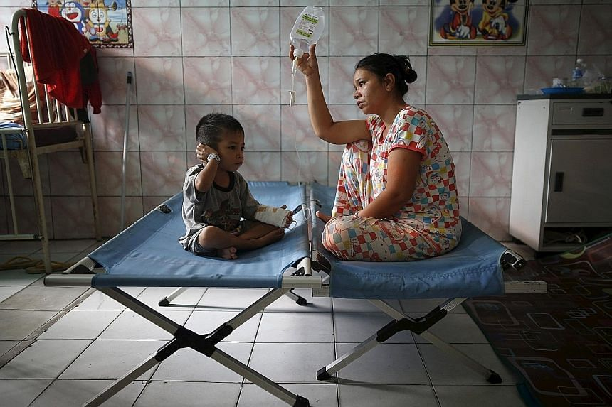 A mother tending to her son, who is recovering from a respiratory illness in a hospital in Palangkaraya, Central Kalimantan, yesterday. The death toll from the haze crisis has risen to 19, including children, in provinces like South Sumatra and Centr