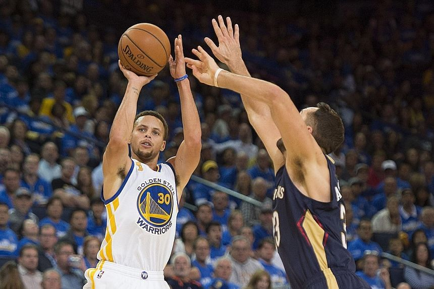 Golden State guard Stephen Curry getting in a shot despite the close attention of New Orleans forward Ryan Anderson. The NBA title holders won 111-95 at the Oracle Arena in Oakland.