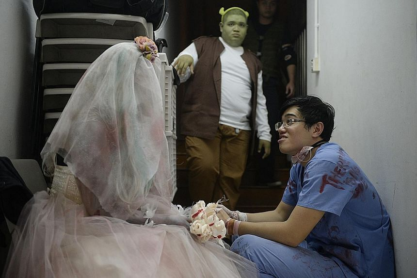 Caleb Tan (right) chats with Danielle Faith Chao, 29, who is dressed as a corpse bride, while Mohamad Taufik Ali, 23, acting as Shrek, stands in the background. Pro-wrestling involves theatrical skill as the shows often have a storyline.