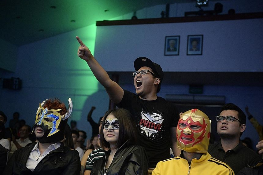 A member of the audience reacts to the action in the ring, while others have fun wearing lucha libre (free wrestling, in Spanish) masks while they watch the show. Currently, SPW draws an average of 400 people per show.