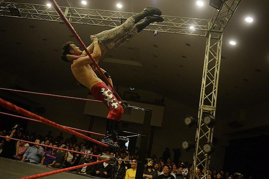 Greg Glorious (Greg Ho), 32, throws The Ladykiller (Dennis Hui) off the top rope. Pro wrestling matches are carefully choreographed and the results are pre-determined.