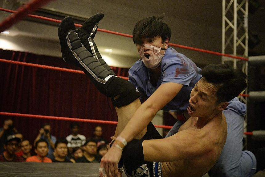 Dr Gore (Caleb Tan in blue doctor's scrubs) tackles opponent Mister Consistency (who wants to be known only by his initials,MK), 25, in a dramatic fashion with both displaying exaggerated expressions of pain, much to the delight of the audience.