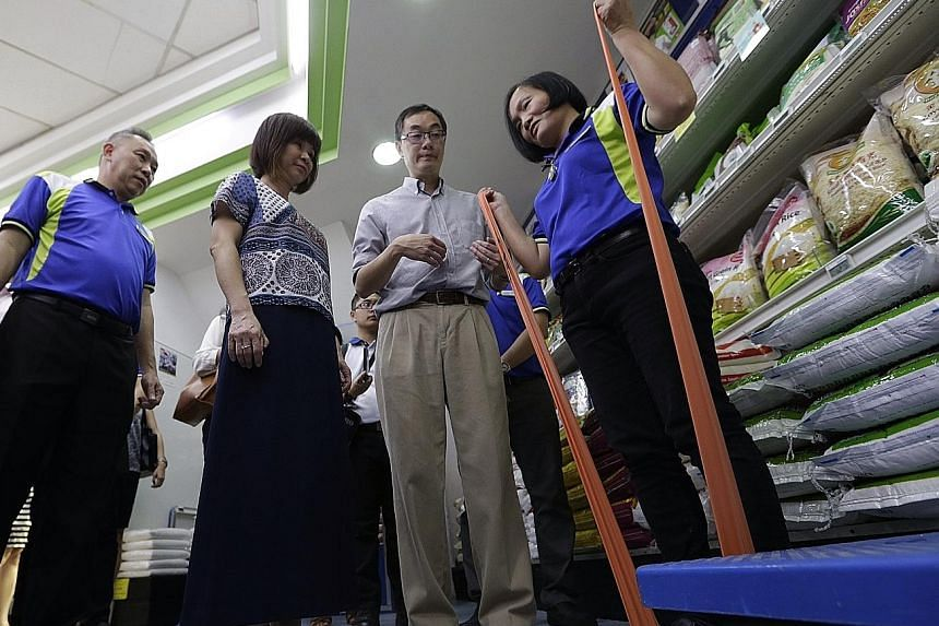 (From left) Sheng Siong CEO Lim Hock Chee, Dr Amy Khor and ST Healthcare medical expert Ng Wee Tong watch as retail assistant Zou Meili, 45, shows them how she does a stretching exercise using a resistance band.