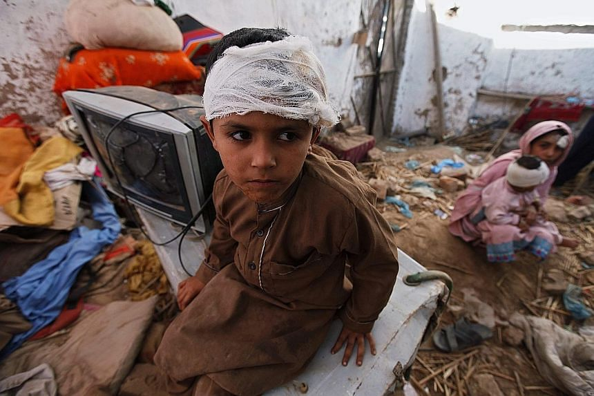 A Pakistani boy who was injured in the earthquake on Monday sitting in his damaged home in Peshawar, Pakistan.