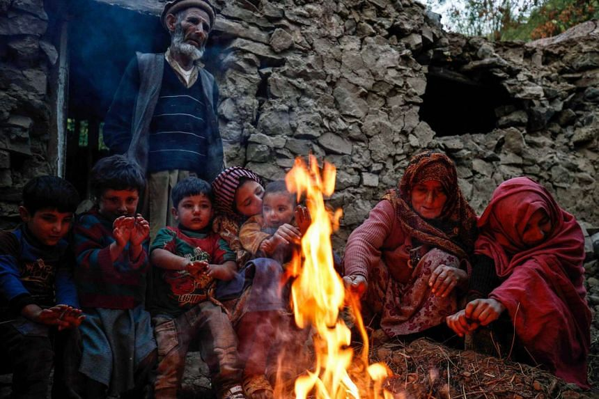 Pakistanis warming themselves round a fire outside their home which was destroyed in the Oct 26 earthquake, in Chitral valley, on Oct 28, 2015.