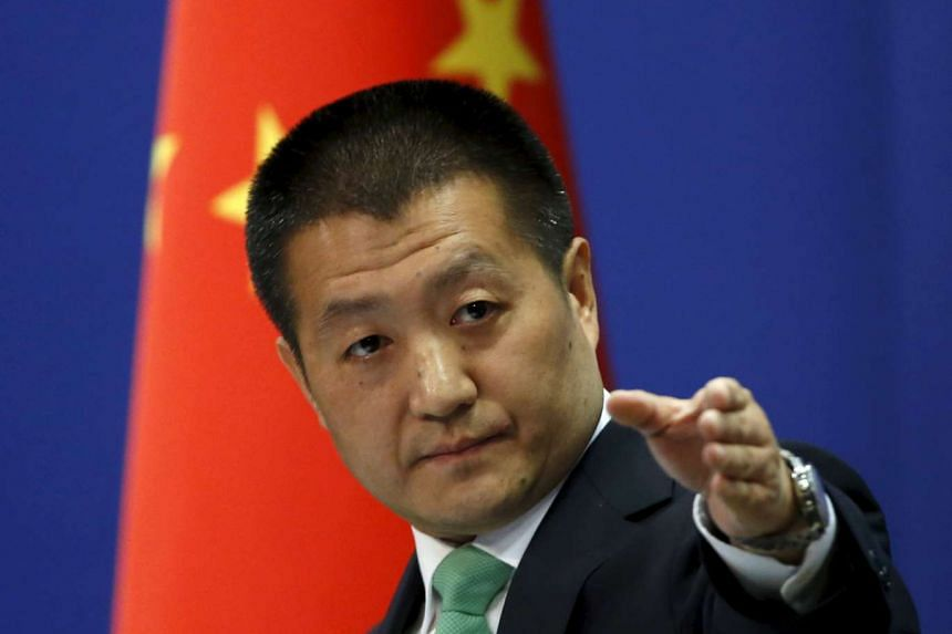 Chinese Foreign Ministry spokesman Lu Kang points out a reporter to receive a question at a regular news conference in Beijing.
