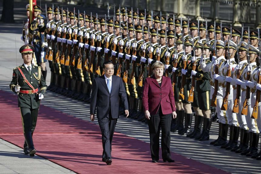 China's Premier Li Keqiang and Germany's Chancellor Angela Merkel (right) inspect honour guards during a welcoming ceremony outside the Great Hall of the People in Beijing.