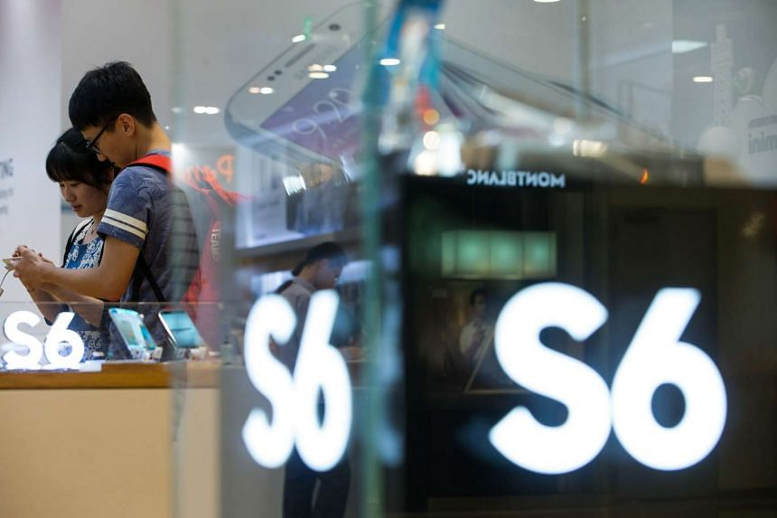 Customers try out a Galaxy S6 Edge smartphone on display at the Samsung's flagship store in Seoul, South Korea.