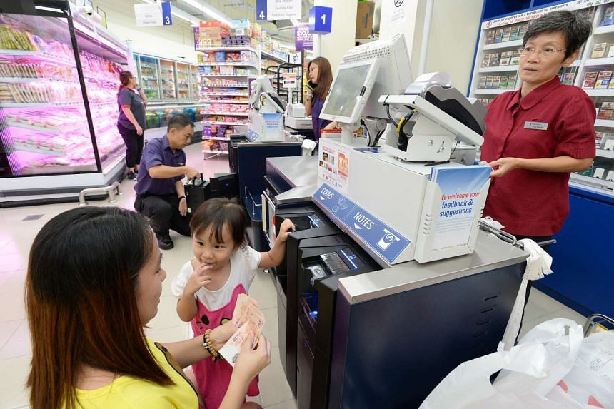 Ms Wu Yinyu, (in yellow) 30, with her daughter Celeste Koh, 3, making payment using the new iCash system at NTUC Fairprice located at Blk 308C Punggol Walk on Oct 28, 2015.