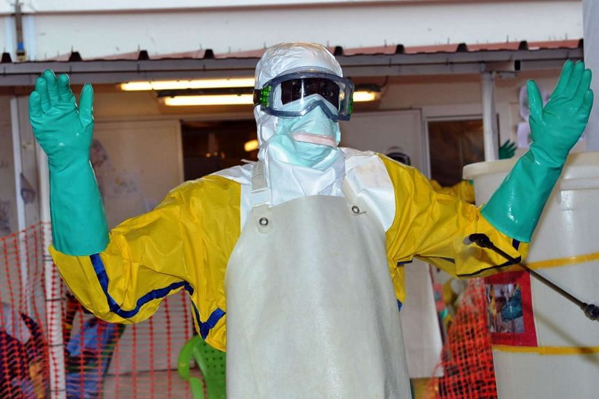 A health worker in protective gear being sprayed with disinfectant at the Nongo Ebola treatment centre in Conakry, Guinea, on Aug 21, 2015.