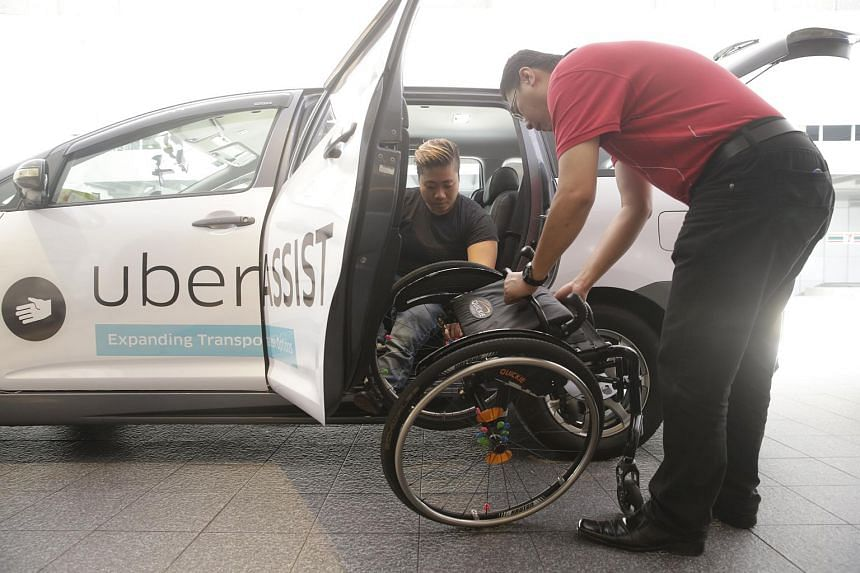 Para-athlete Theresa Goh being assisted by Uber driver Alson Tay with her wheelchair at the launch of UberAssist.