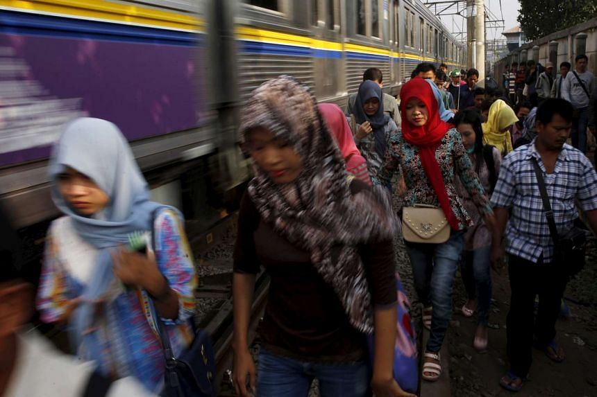 Indonesian workers walk on train tracks as they go to work at Tanah Abang train station in Jakarta, on Oct 15, 2015.