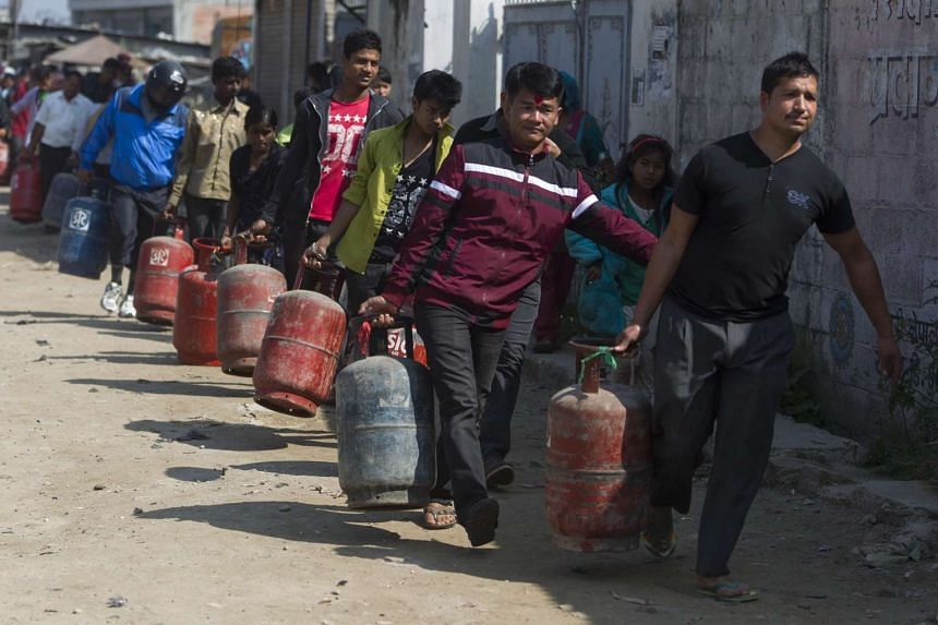 Nepalese people carry empty cooking gas cylinders for fresh supply in Kathmandu, Nepal, Oct 20, 2015.