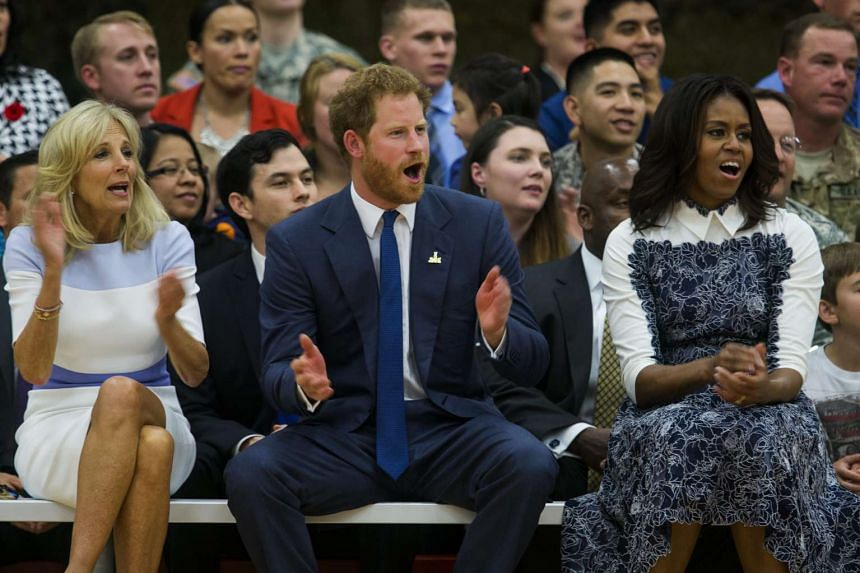 Britain's Prince Harry (centre), US First Lady Michelle Obama (right), and Dr Jill Biden (left) watching wounded American veterans play basketball at an event to promote the 2016 Invictus Games, at Fort Belvoir, Virginia, on Oct 28, 2015.