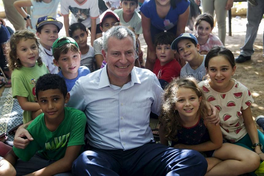 Arab and Jewish children from the Hand in Hand Jewish-Arab integrated bilingual schools pose with New York City Mayor Bill De Blasio during an olive harvesting event west of Jerusalem on Oct 17.