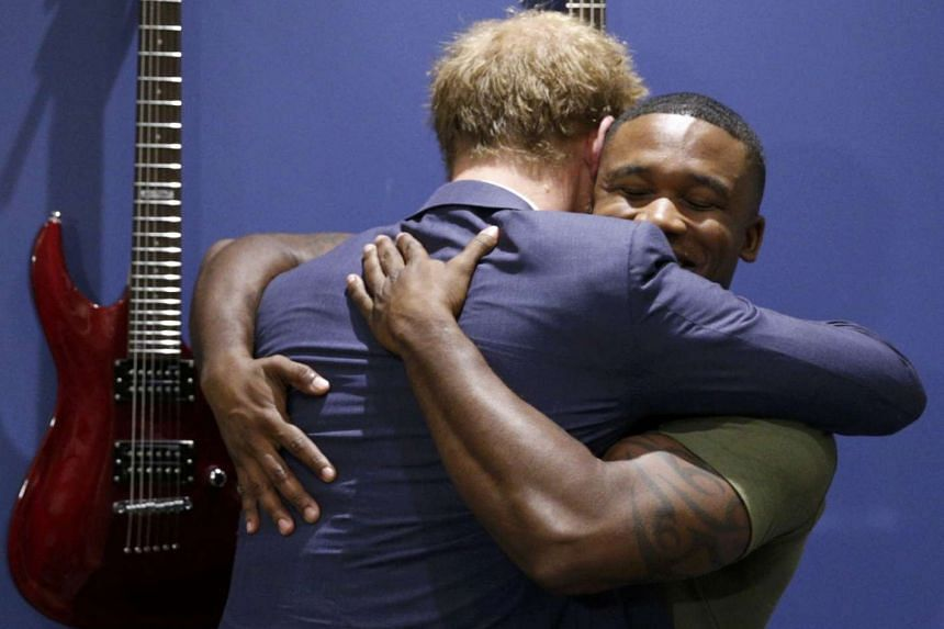 Britain's Prince Harry (left) embraces US Marine Roderic Liggens while meeting with wounded servicemen at Fort Belvoir, Virginia, on Oct 28, 2015.