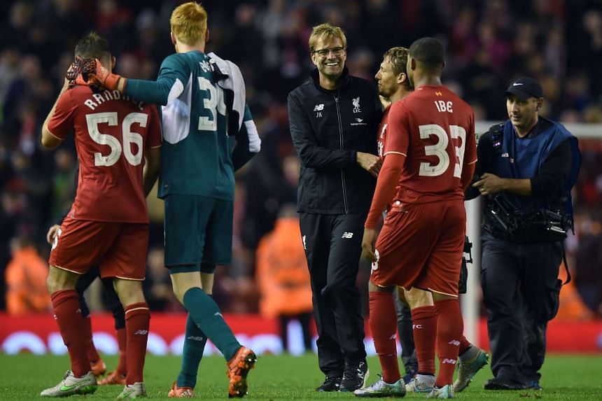 Jurgen Klopp (centre) shares a moment with Lucas Leiva (third from right) following the English League Cup fourth round football match between Liverpool and Bournemouth.