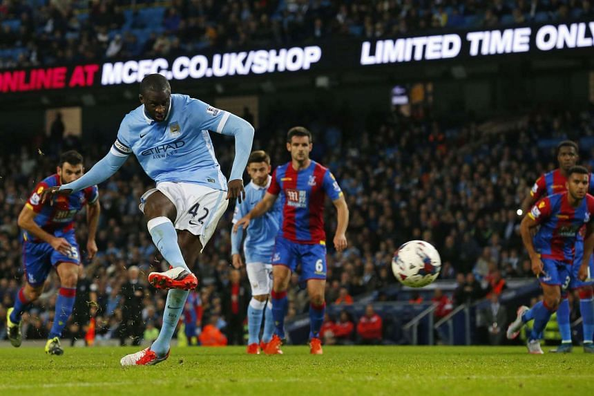 Manchester City's captain Yaya Toure scores their fourth goal from the penalty spot during the English League Cup fourth round football match between Manchester City and Crystal Palace.