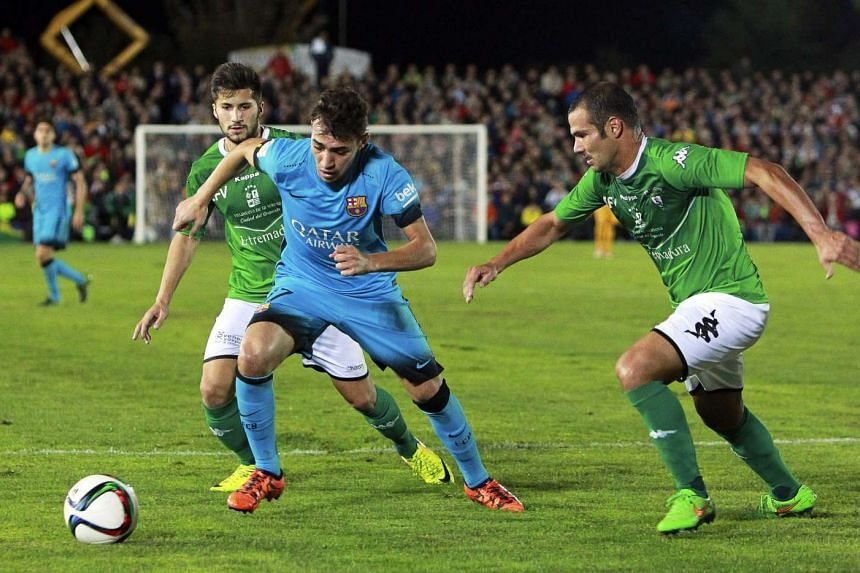 Barcelona's striker Munir El Haddadi (centre) in action against Villanovense players Victor Calatrava (left) and Angel Mato 'Anxo' (right) during the Spanish King's Cup fourth round football match.