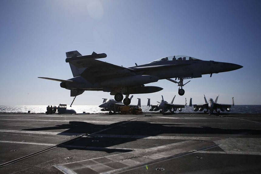 A US Navy F/A-18 Super Hornet fighter lands onto the deck of the USS Ronald Reagan, a Nimitz-class nuclear-powered aircraft carrier, during a joint naval drill between South Korea and the US in the West Sea off South Korea on Oct 28, 2015.