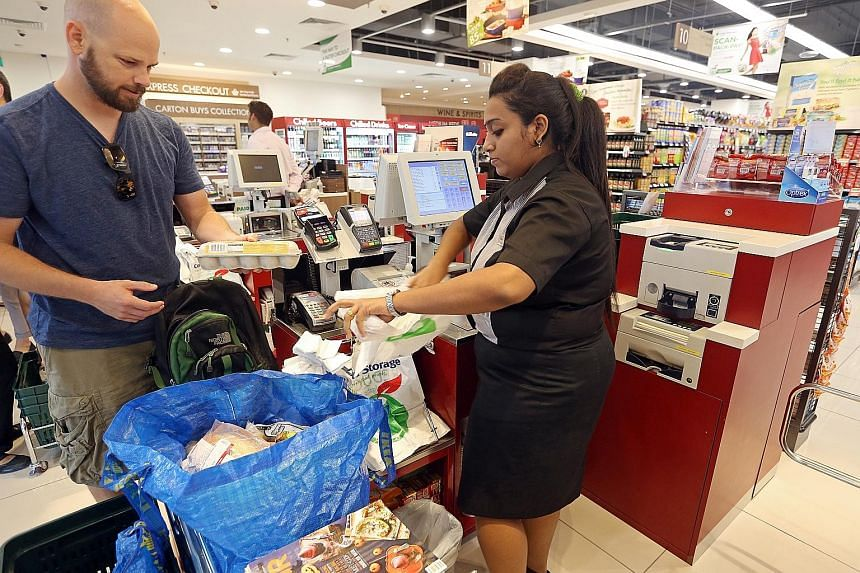 A Cold Storage employee at Sime Darby Centre helping a shopper scan and pack his purchases. The supermarket chain plans to launch the new cash-collection system at two other stores in the next few months. FairPrice, Cheers and Sheng Siong are also in