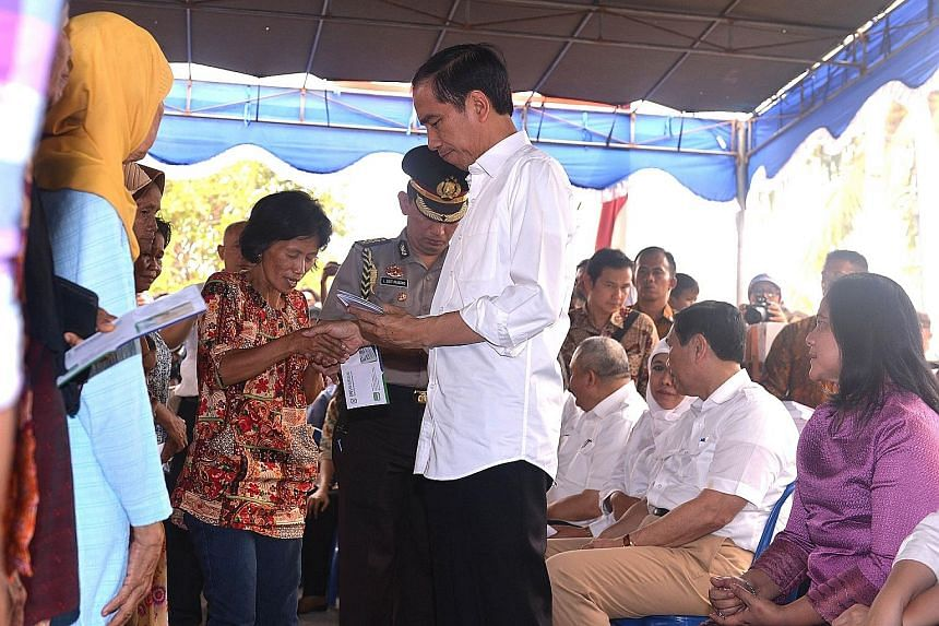 Indonesian President Joko Widodo handing out healthcare cards and compensation yesterday to families who have lost loved ones due to the haze in Kayuagung, South Sumatra.