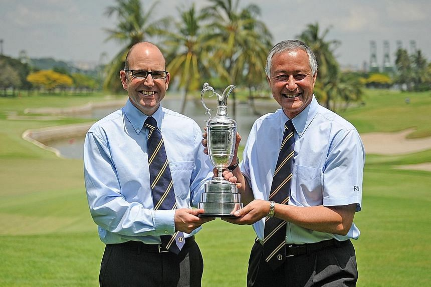 Grant Moir (far left), the R&A's director (rules of golf) and David Bonsall, the chairman of the organisation's rules of golf committee, holding the British Open trophy.