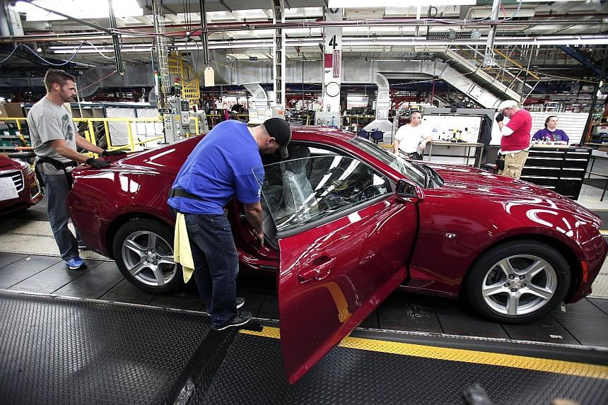 Workers on Monday putting finishing touches to a new General Motors 2016 Chevrolet Camaro at GM's assembly plant in Lansing, Michigan. Investors are now waiting for third-quarter US GDP and non-farm payroll data on Nov 6 to see if there is a case for