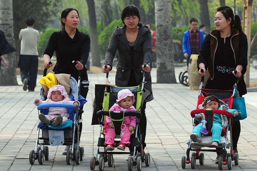 Women pushing babies in prams through a Beijing park in 2011.
