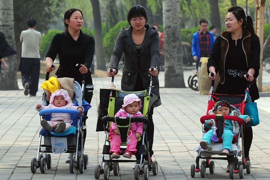 Women pushing babies in prams through a Beijing park in 2011.