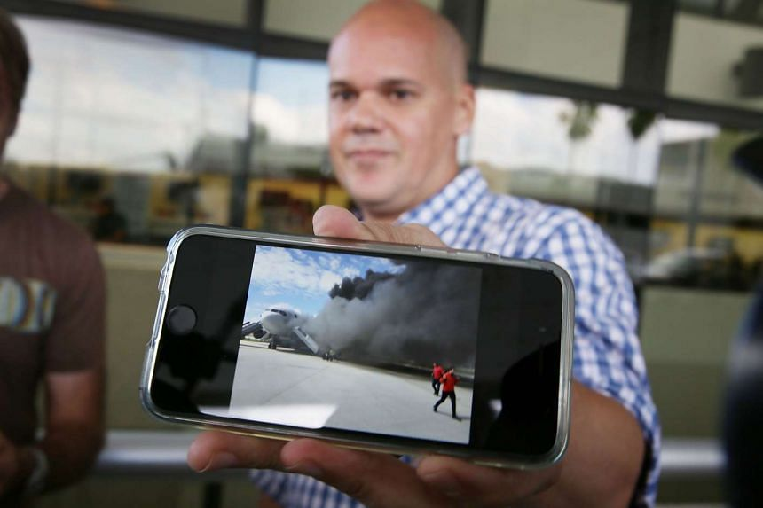Passenger Andres Gallegos showing a picture he took of the burning plane as he evacuated on the tarmac.