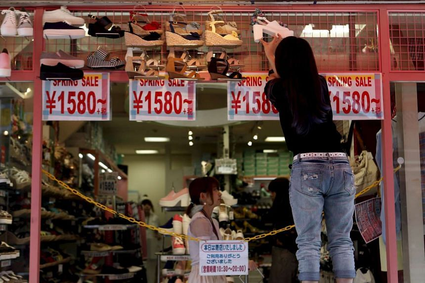 A shop clerk displays shoe price tags as she prepares to open a shoes store at Tokyo's Harajuku shopping district, Japan, on Apr 30, 2015.