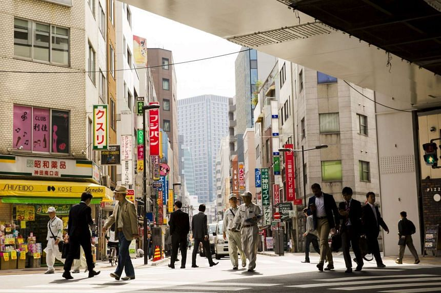 People crossing a street at a business district in Tokyo on Oct 30, 2015.