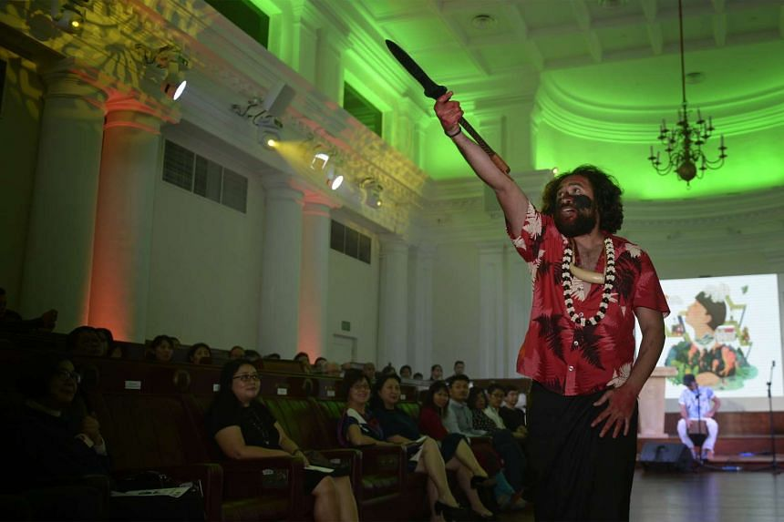 """Daren Kamali holds a Wau, a Fiji warrior weapon, and performs """"Stories from Islands, Songs from Islanders 2"""" during the official launch of the Singapore Writers Festival 2015 on Oct 30, 2015."""