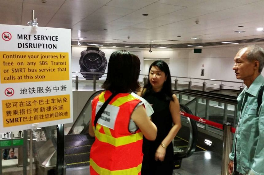 Commuters talking to a staff member at Serangoon MRT during the service disruption on Oct 26, 2015.