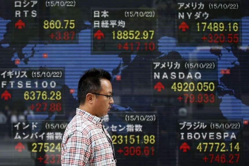A man walks past an electronic board showing the stock market indices of various countries outside a brokerage in Tokyo, Japan, Oct 23, 2015.