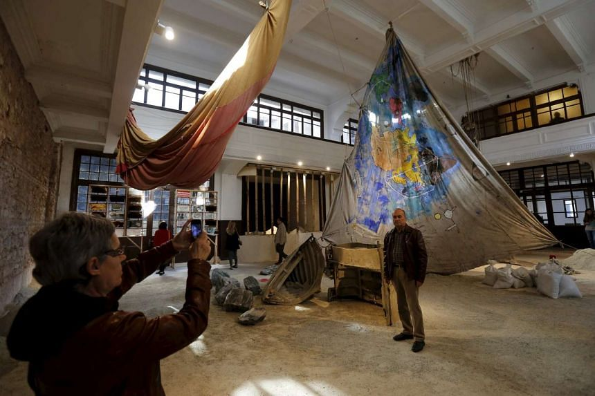 A visitor posing for a photo with Anna Boghiguian's work The Salt Traders at the 14th Istanbul Biennial on Oct 28, 2015.